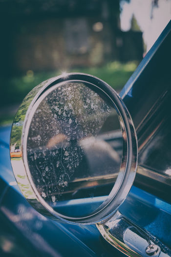Close-up of reflection on side-view mirror of car