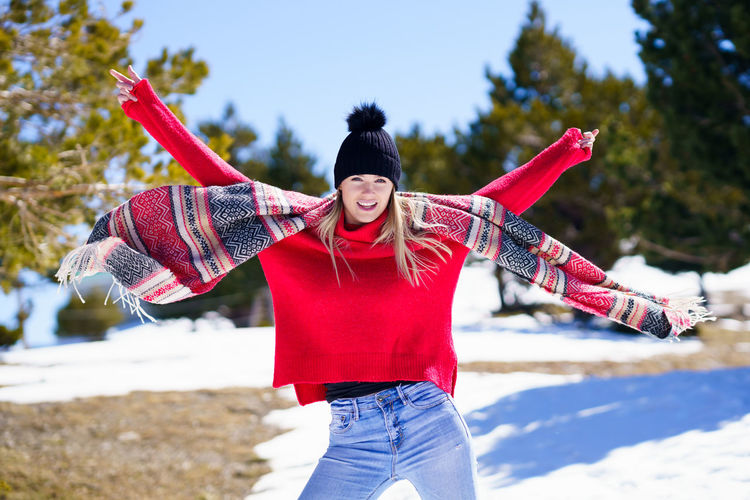 Midsection of woman with arms raised standing outdoors