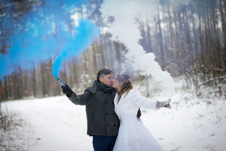 Smiling Wedding Couple Holding Distress Flares While Standing At Forest During Winter