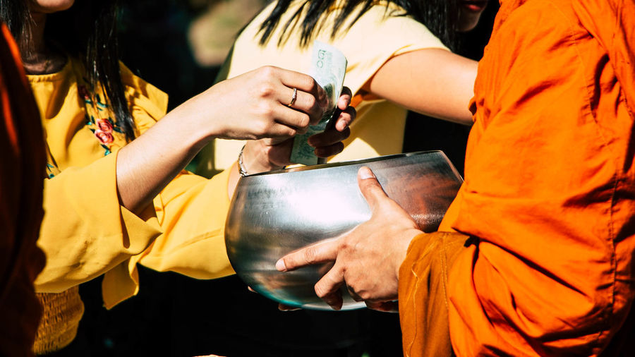 Midsection of woman giving money to monk