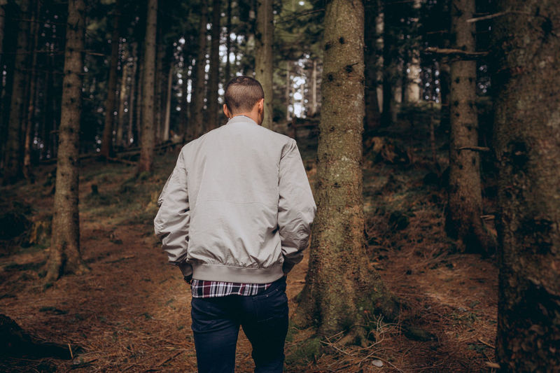 Young man is walking trough the dark forrest EyeEm Best Shots EyeEm Selects EyeEmNewHere Love Adult Casual Clothing Day Forest Land Leisure Activity Lifestyles Men Nature One Person Outdoors Plant Real People Rear View Standing Three Quarter Length Tree Tree Trunk Trunk WoodLand