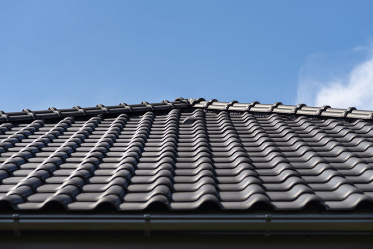 The roof of a house covered with a new ceramic tile, visible ceramic ventilation tile on the roof.