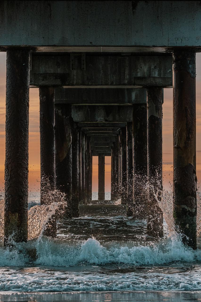 WATER SPLASHING ON BRIDGE AGAINST SKY AT SEA