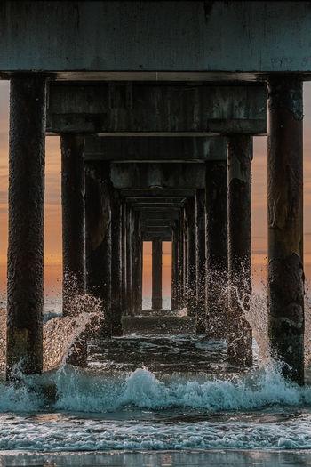 Water splashing on bridge against sky