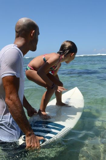 Instructor teaching girl to surf in sea