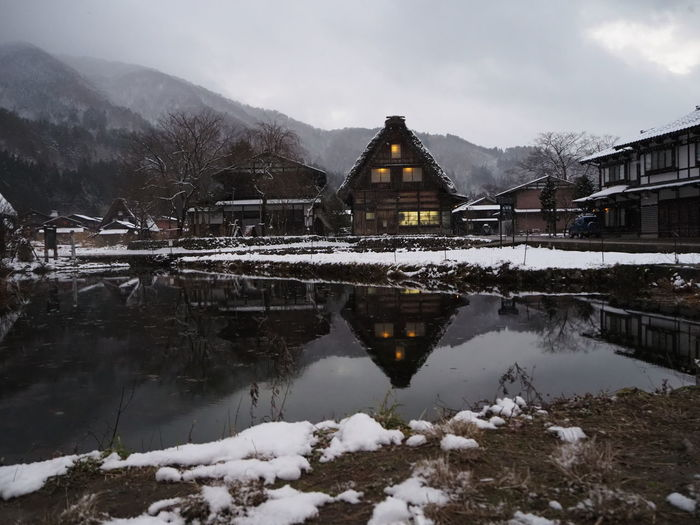 Reflection of house on lake against sky during winter