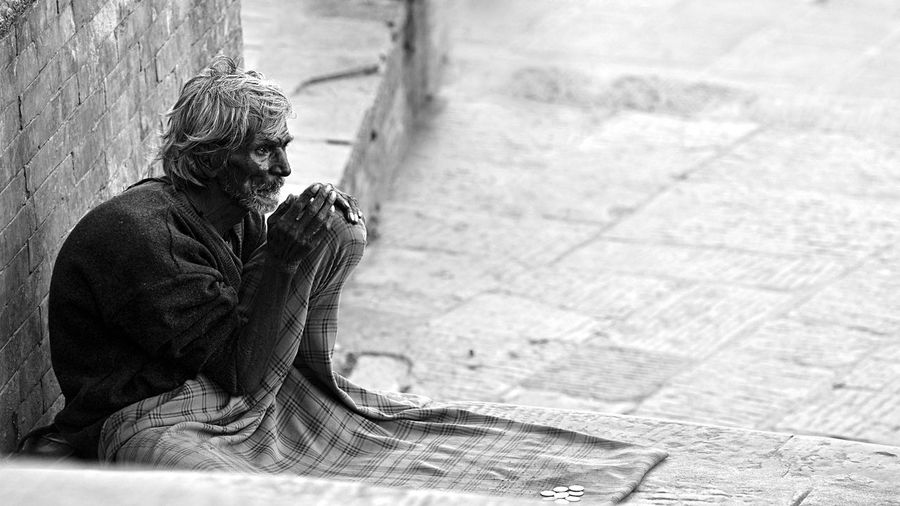 Old man sitting at sidewalk against wall