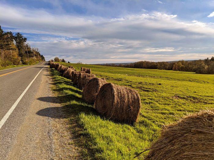 Hay bales on field by road against sky