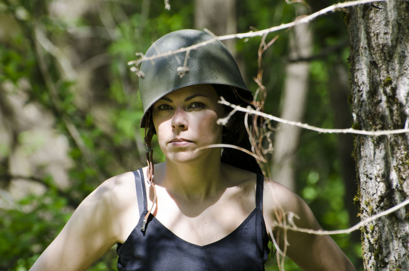 Portrait of serious woman wearing army helmet while hiking in forest