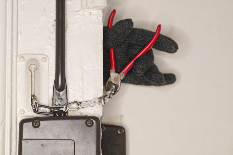 Cropped hand of burglar cutting chain on door with pliers