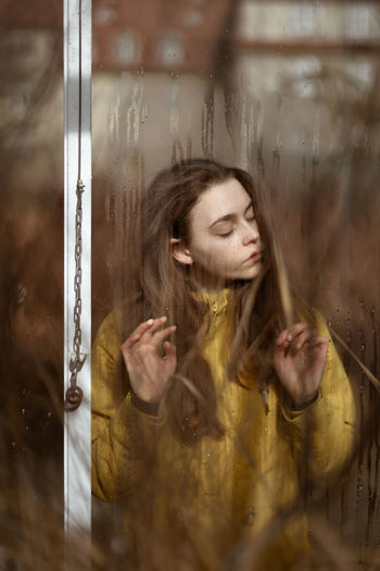 Portrait of young woman with reflection on glass