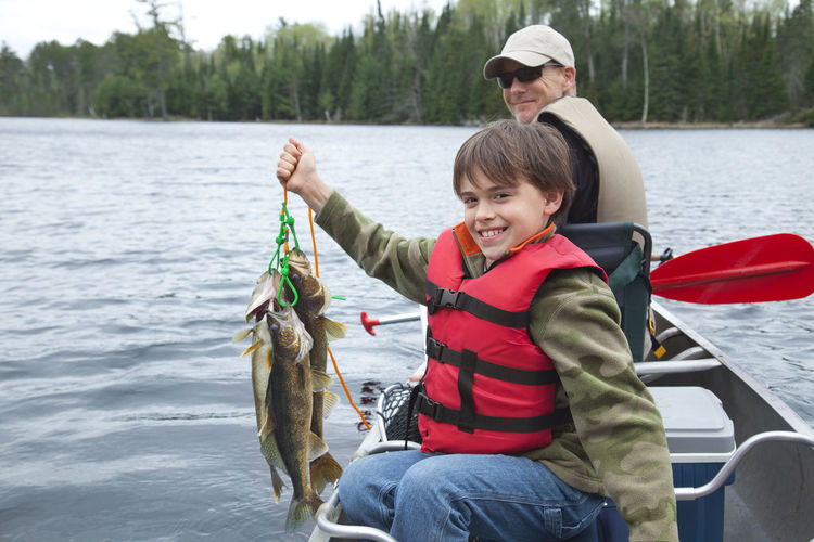 Portrait Of Happy Boy With Father Holding Dead Fish In Boat On Lake