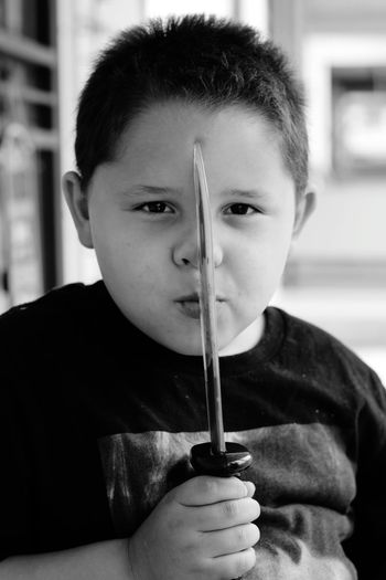 Portrait of boy holding knife sitting at home