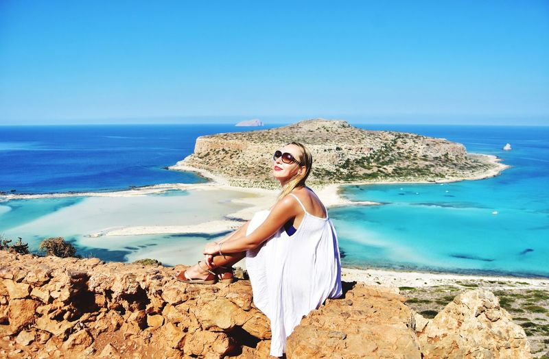 Woman wearing sunglasses sitting against sea