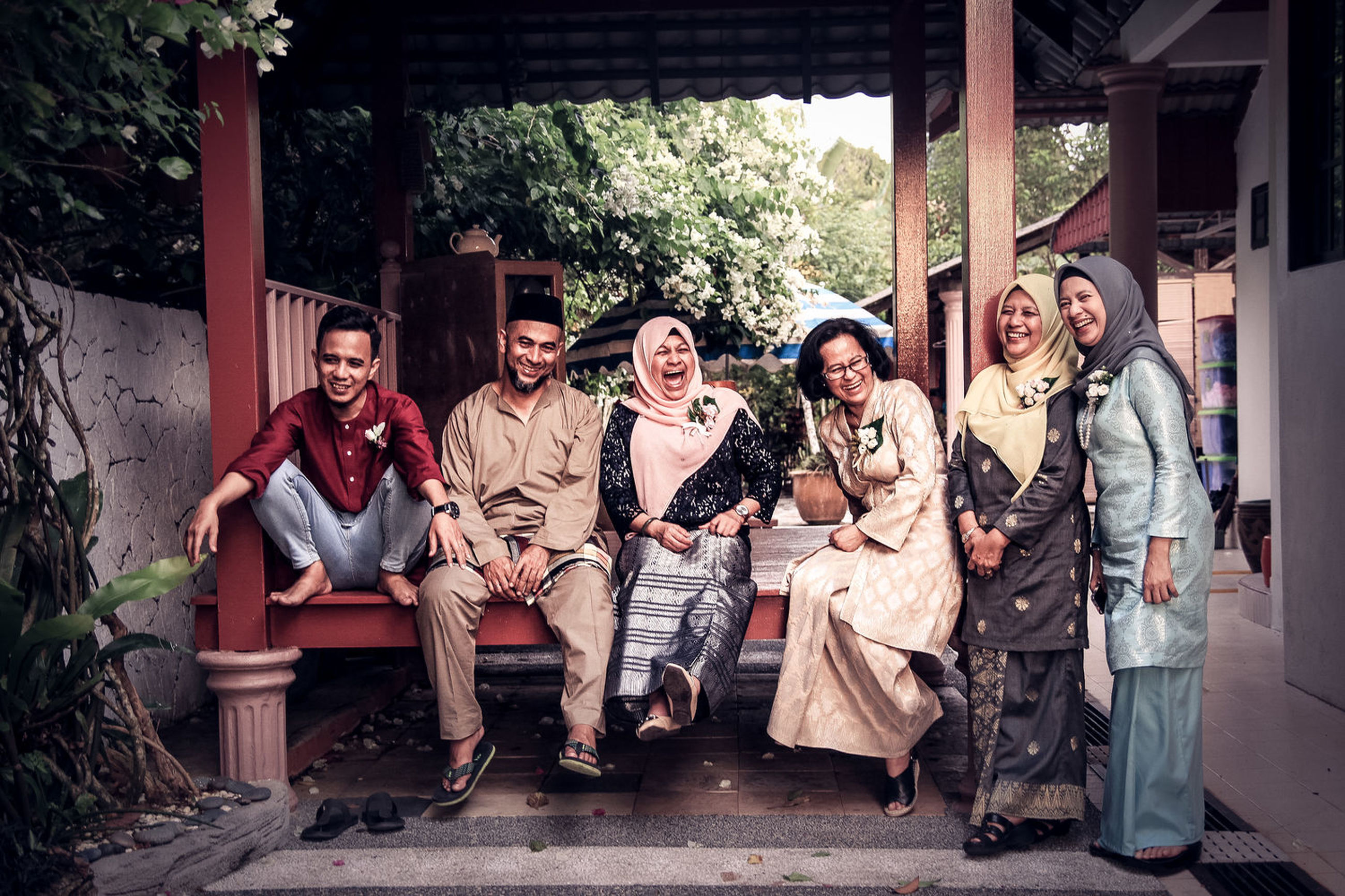 smiling, full length, happiness, group of people, emotion, portrait, togetherness, sitting, men, adult, looking at camera, young adult, front view, real people, young women, women, casual clothing, young men, architecture, people, outdoors, mature men