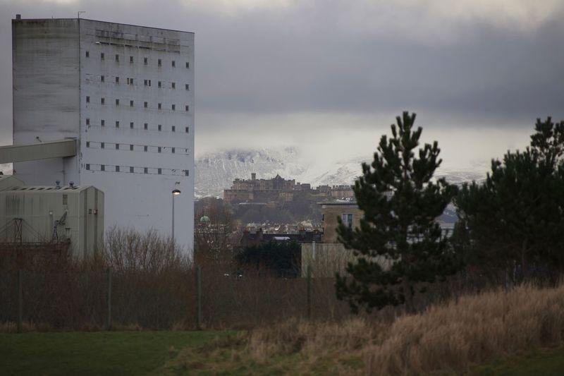 Buildings on field against sky