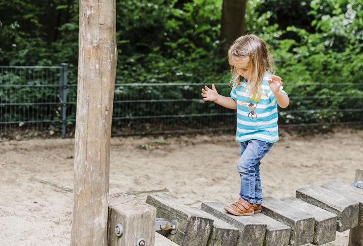 Full length of girl walking on wooden bridge at park