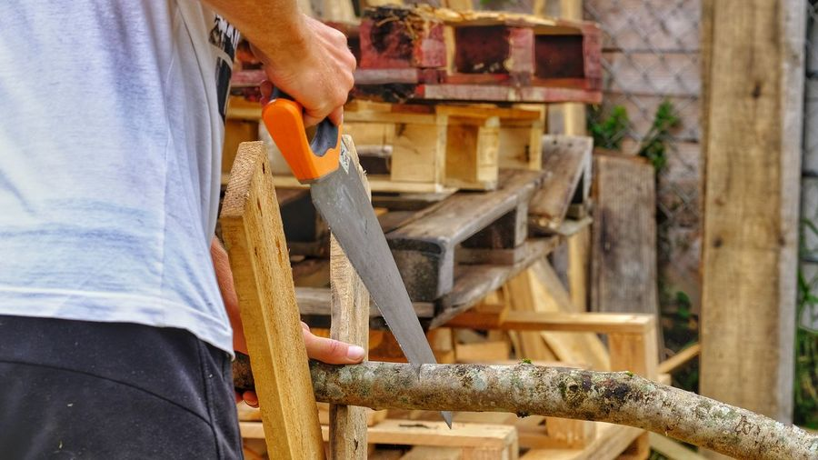Low section of man working on wood