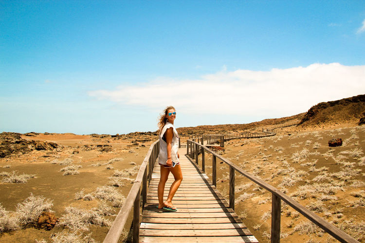 Portrait of young woman standing on boardwalk against blue sky during sunny day