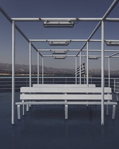 Empty benches against clear sky