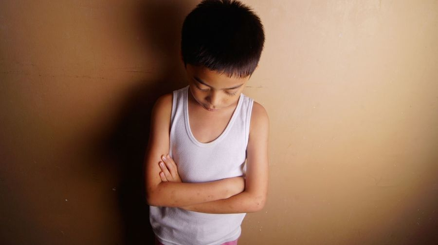 Boy With Arms Crossed Standing Against Wall At Home