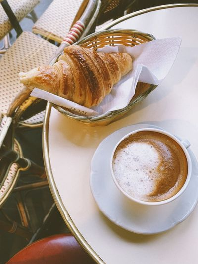 High angle view of coffee with croissant on table in cafe