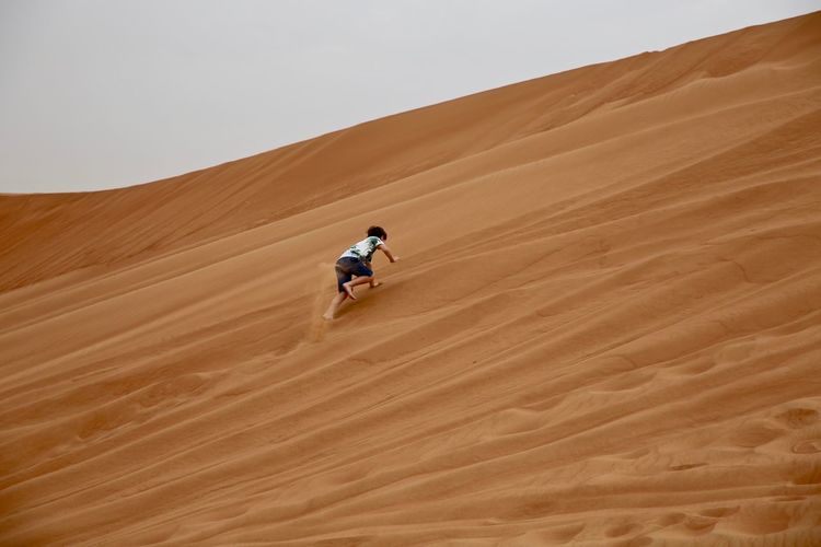 Low angle view of boy climbing on sand dunes at desert