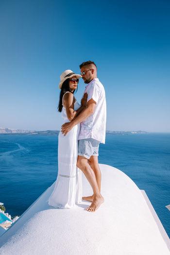 Couple kissing against sea against clear blue sky