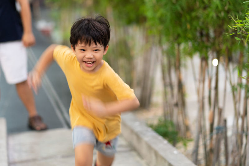 Boys Casual Clothing Child Childhood Day Emotion Enjoyment Focus On Foreground Happiness Innocence Leisure Activity Lifestyles Males  Men Outdoors People Real People Running Shorts Smiling Three Quarter Length Two People