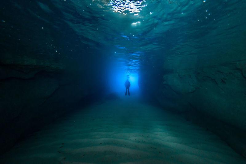 Silhouette person swimming in sea