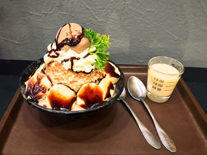 Bingsu with topping such as Chocolate icecream, banana, wipping cream, vegetable on cup with Condensed milk and spoon put on tray. Patbingsu, Korean shaved ice dessert, Kakigori. Frozen Dessert. Banana Bingsu Chocolate Chocolate Condensed Milk Bingsu Dessert Eating Utensil Food Food And Drink Freshness Frozen Dessert Ice Cream Icecream Kakigori Korean Shaved Ice Dessert Patbingsu Plate Ready-to-eat Spoon Sweet Sweet Food Table Tray Wipcream Wipping Cream