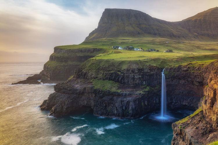 Mulafossur Waterfall in Faroe Islands Beauty In Nature Cloud - Sky Eroded Faroe Islands Flowing Water Idyllic Land Motion Mountain Múlafossur Nature No People Non-urban Scene Outdoors Rock Rock - Object Rock Formation Scenics - Nature Sea Sky Solid Tranquil Scene Tranquility Water Waterfall