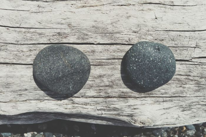 Stones on some beach wood. The OO Mission Beachwood Stones Wood Two Lined Up In A Row Round Smooth