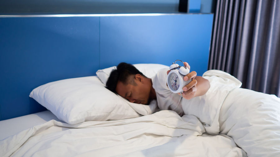 Man with alarm clock sleeping on bed at home