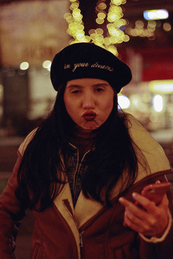 NYC, 2018 Lifestyles Portrait One Person Real People Leisure Activity Front View Looking At Camera Clothing Night Hat Waist Up Focus On Foreground Young Adult Standing Illuminated Young Women Women Casual Clothing Hairstyle Teenager Beautiful Woman Warm Clothing Beret Fashion NYC New York Winter Makeup Face Bokeh The Portraitist - 2019 EyeEm Awards