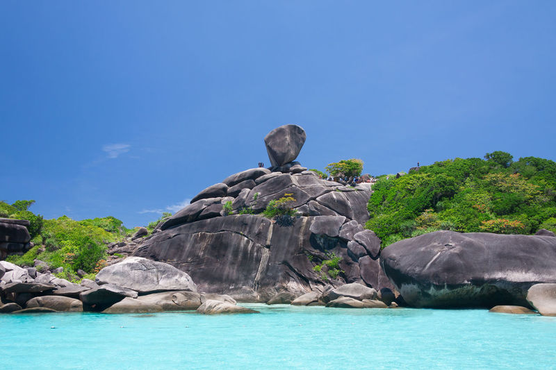 Rock formation in sea against blue sky