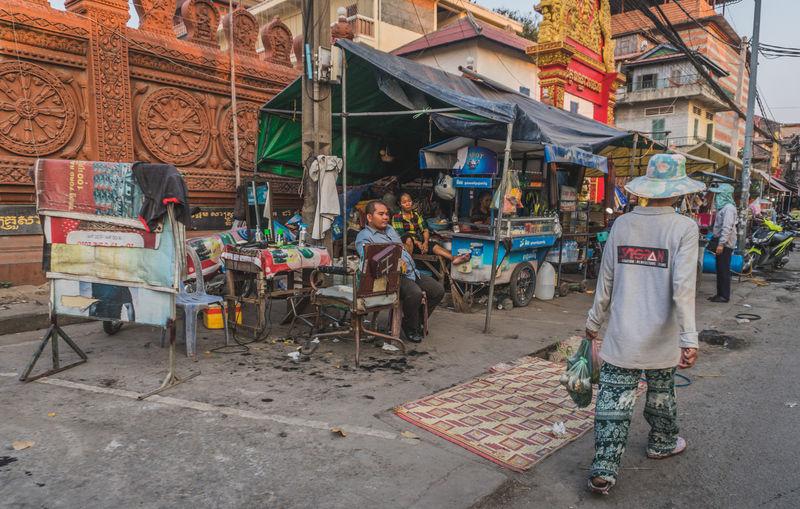 Rear view of people working on street against buildings