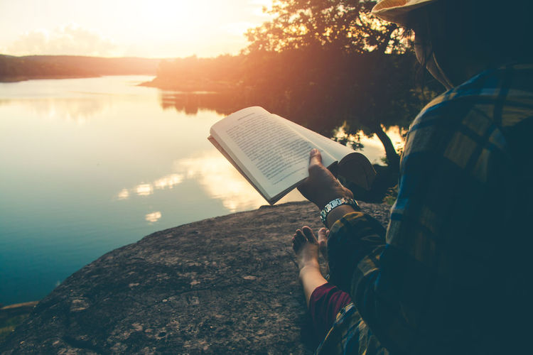 Rear view of man reading book on rock by lake against sky