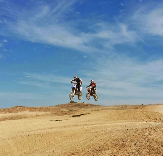 Motocross racers in mid-air on sandy field against sky