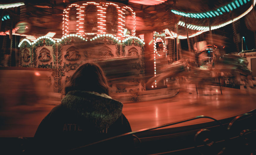 Rear view of woman in illuminated carousel at night