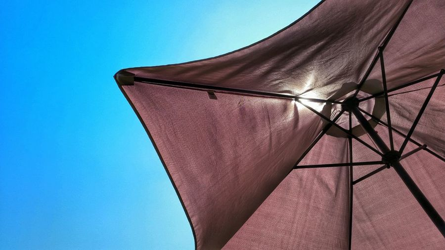 Low angle view of beach umbrella against clear sky
