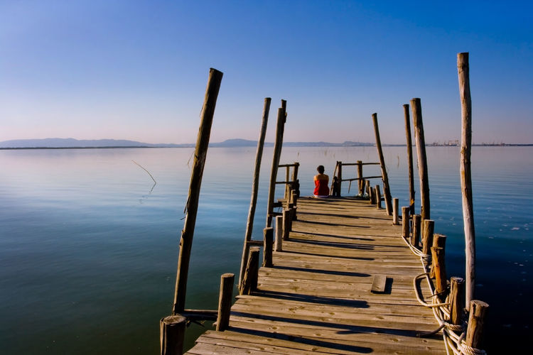 Happiness is sitting on the end of a pier EyeEmNewHere Tranquility Vacations Beauty In Nature Fishing Happyness Horizon Over Water Nature One Person Outdoors Pier Scenics Sea Tranquil Scene Tranquility Water Wood - Material
