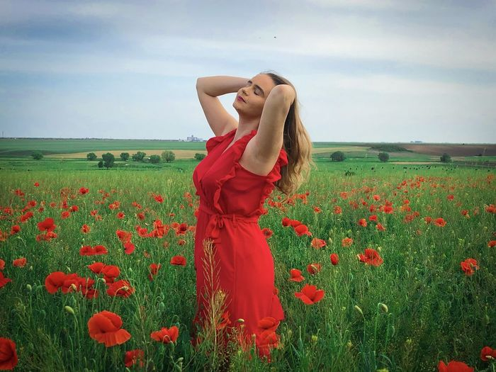 Rear view of young woman with red poppy flowers in field