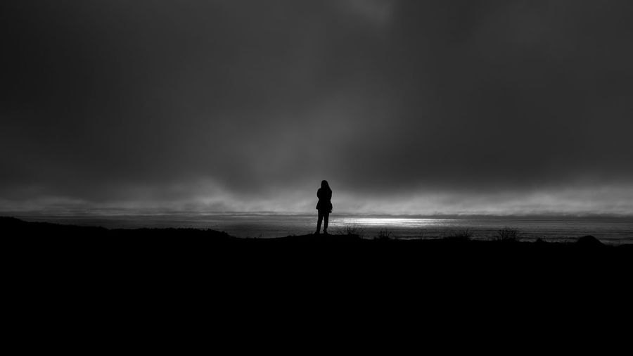 Silhouette Woman Standing On Field Against Cloudy Sky