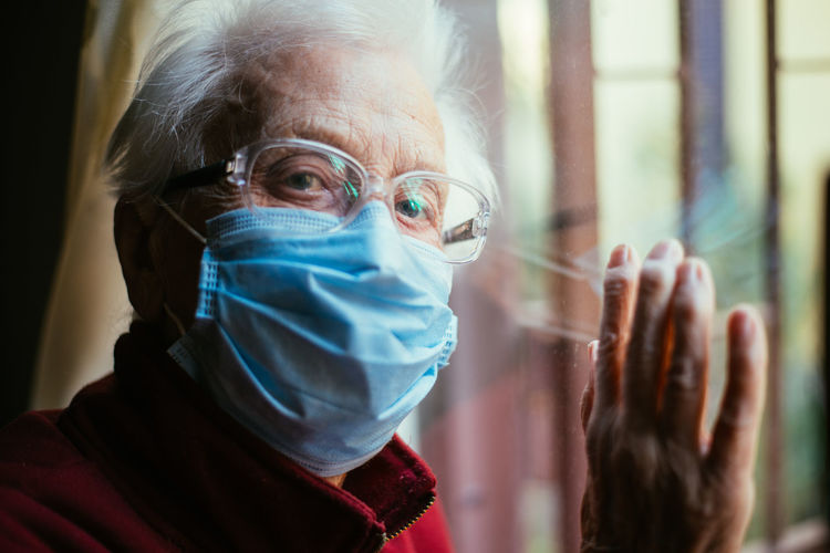 Close-up portrait of senior woman wearing mask with reflection on window