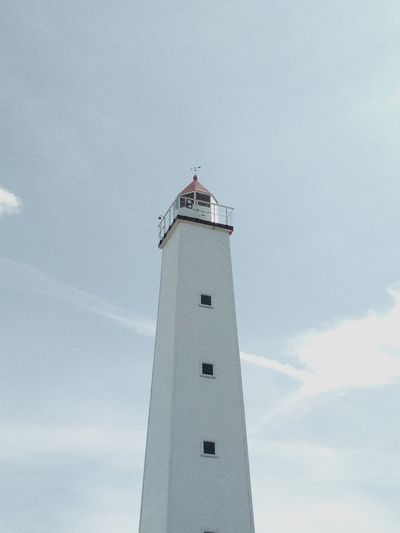 Low angle view of lighthouse by building against sky