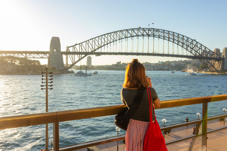 Rear View Of Woman Looking At Sydney Harbor Bridge Over River Against Sky