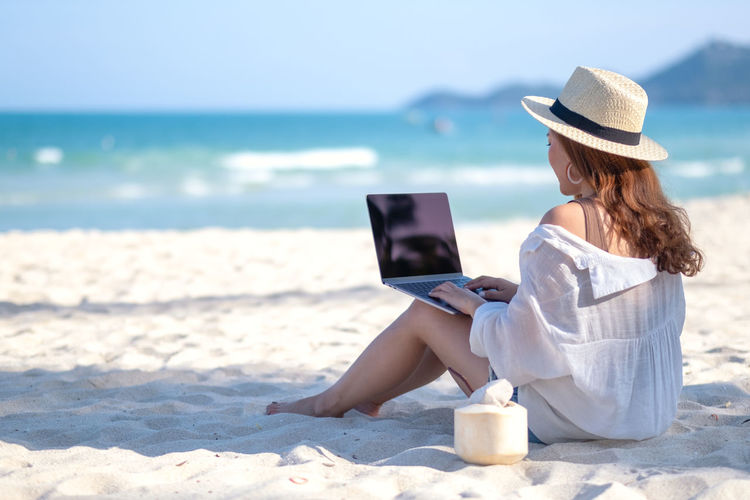 A woman using and typing on laptop computer keyboard while sitting on a beautiful beach Background Beach Beautiful Black Blue Coconut Communication Computer Connection Copy Copyspace Desktop Device Display Empty Female Girl Hand Holding Holiday Internet Laptop Leisure Lifestyle Look Message Nature Notebook Online  Over People person Relax Sand Screen Sea Shoulder Sitting Sky Space