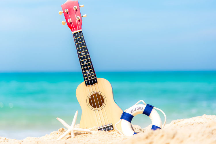 Low angle view of guitar at beach against sky