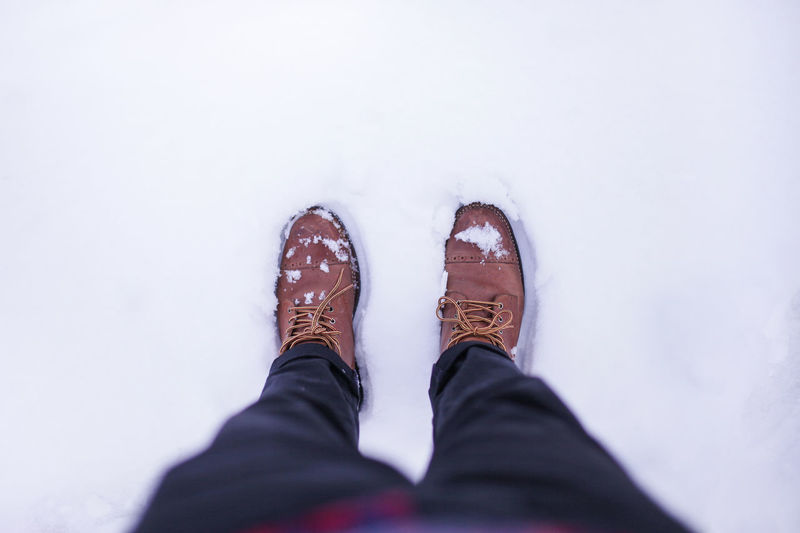 Winter boots on icy ground. Shoe Low Section One Person Human Leg Human Body Part Personal Perspective Body Part Snow Winter Standing Men Cold Temperature High Angle View Real People Lifestyles Day Directly Above Clothing Human Foot Jeans Leather Human Limb Ice White Winter